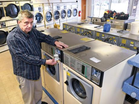 Randy Howell owner of Wash and Go laundromat holds one of the broken coin boxes on his washing machines Wednesday afternoon in Bloomsburg.