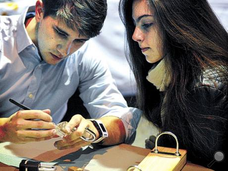 Bloomsburg University senior Rio Weber and Lehigh Carbon Community College student Kelsey Cicchetti work on picking a padlock in the Lock Pick Village event during BloomCON at Bloomsburg University on Friday. The two-day conference is hosted by the Bloomsburg University Digital Forensics Club.