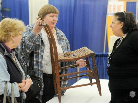 TV personality and antiques appraiser Dr. Lori Verderame, right, talks with Mary Vosburg Grega, left, and Julia Anthony about Anthony's chair from the 1820-1830s on Friday afternoon at the Bloomsburg Fairground during the 30th Anniversary Home & Outdoor Living Show. Dr. Lori will be doing antique appraisal show Saturday at noon, 3 p.m. and 6 p.m. and Sunday at 11 a.m.