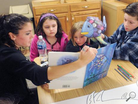 "Bloomsburg University student Amber Csrenko reads the book, ""The Rainbow Fish,"" to, from left, Jenna Kull, Izzy Marks and Jack Marks during Danville Child Development Center's reading night Wednesday night. This was the second session this week in which students from Bloomsburg University came down to read to the children."