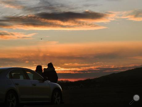 Tristin Gray, left, and Brianna Fuller sit on the hood of their car along the boat access road next to the airport while watching a plane take off into the western sunset Monday evening.