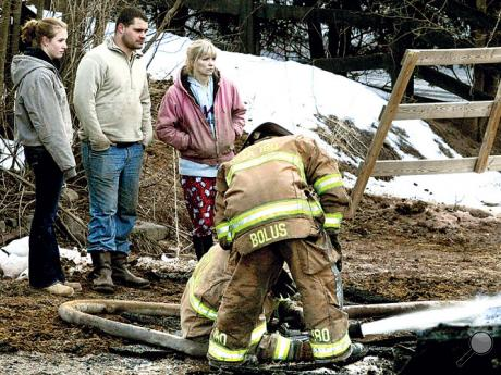 Michelle Brown, standing in background third from left, 42, and two family members watch firefighters extinguish a fire that destroyed the family's horse barn in South Centre Township on Thursday morning.