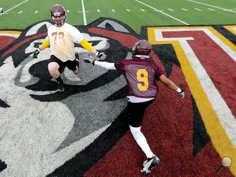 Bloomsburg University's Shawn Secola, left, reaches for the hand of Connor Gades as the pair cross in the center of Danny Hale Field while stretching out during warm up during the first day of spring football at the university.