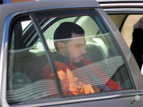 Cea Jay Chattin, of Benton, sits in the backseat of a police car following his arraignment at District Judge Doug Brewer's office in Millville on Sunday afternoon.