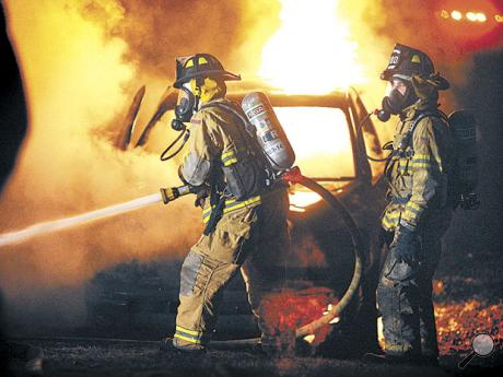 Espy firemen Jonathan Shannon, left, and Cody Fronk take part in battling an early-morning fire at the home of James and Patty Harvey at 39 Hofnagle School Road in Mifflin Township on Thursday. Behind them is a burning pickup truck.
