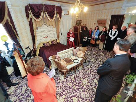 Johannah Naus, Jackson Mansion coordinator, center with red dress, talks about how Mrs. Jackson used her bedroom while she stands in it with directors, officers and employees of the First Columbia Bank and Trust Co.