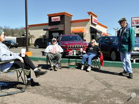 Friends, from left, Susan Prisuta, Ron Parks, Carla Parks and Dick Sweeney sit in the parking lot next to the Dunkin' Donuts in Bloomsburg on Friday afternoon, enjoying each other's company while maintaining their social distancing.