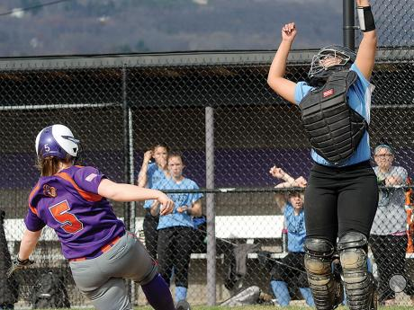Danville's Ally Mullen left, scores as Midd-West's catcher Jennasis Mosley misses a high throw Thursday afternoon in Danville.
