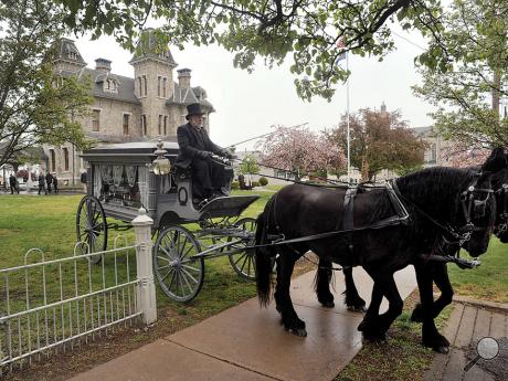 Joe Tetz maneuvers his team of horses as they leave the lawn of the Jackson Mansion with the hearse taking the body of Gerald L. Kershner to his final resting place at the Pine Grove Cemetery Friday afternoon in Berwick.