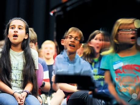 "Danville Saint Joseph's Catholic School student Mehak Kotru, left, sings ""Fireworks"" by Katy Perry as some of her fellow choral festival members are reflected in the piano on stage at Danville Middle School Friday. Over 160 elementary school students participated in the PMEA Elementary school Chorus Festival."