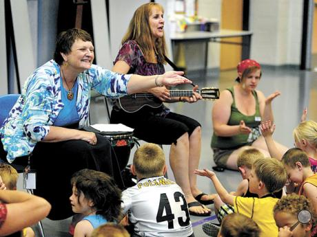Retiring director of the Danville Head Start program Susan Blake blows a kiss to the students as they sing a song in her honor on Thursday. Leading the children is artist-in-residence Mary Knish. Blake worked at Danville Head Start for 25 years, the last 12 as director.