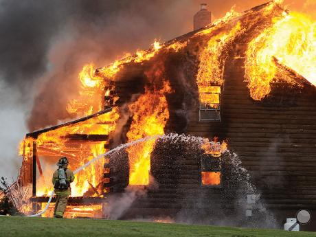 A firefighter works to get one of the first hoselines working as flames engulf a log home off Ellis Turner Road in Mount Pleasant Township Thursday evening.