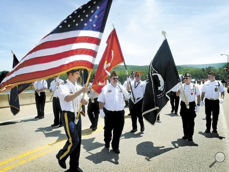 Members of the Nescopeck-Berwick Memorial Day parade color guard stop on the Susquehanna River bridge for a flower-dropping ceremony on Sunday.