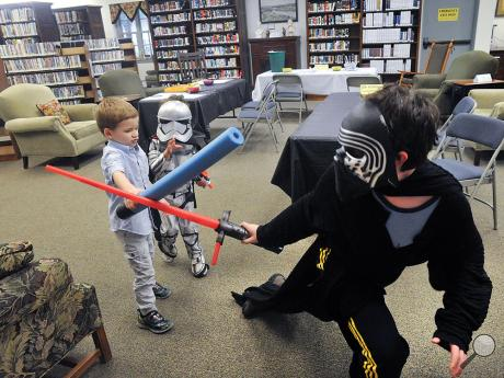 A lightsaber battle brakes out between, from left, James Hnylanski, 6, Jack Adams, 4, and Reid Keck, 11, during the Bloomsburg Public Library's May the Fourth celebration of Star Wars on Wednesday afternoon.