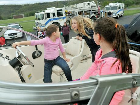 From left, Emma Whitebread, 7, Nevaeh Hottenstein, 6, and Emily Detterbeck, 9, sit in one of the Pennsylvania Fish and Boat Commission's patrol boats Thursday evening during Safety Night, held in front of the Central Columbia Elementary School.