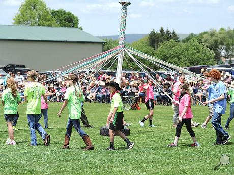 Members of the sixth-grade class in Benton Area School Districtcircle the May Pole during Wednesday afternoon's May Day event near Benton Elementary School.