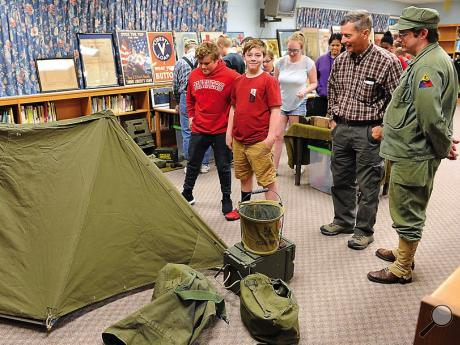 Chris Emery, right, and Todd Lehman, talk to Bloomsburg Middle School students about some of the World War II items that were brought to the school by the members of the Endless Mountains Military Museum on Tuesday morning. Local veterans spent theday talking to the students about their experiences in World War II and Vietnam.