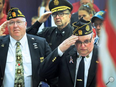 Veterans, from left,Mike Schmidt, John Troychock and Ron Utt, salute the American Flag as the colors are placed at the Danville Primary School's annual Memorial Day program Thursday.