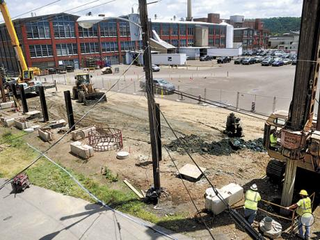 Workers drill holes, at right, and set pilings, at left, along West Fifth Street in Bloomsburg on Monday for the $30 million flood control wall to protect Autoneum, in background, and the former Windsor Foods plant.