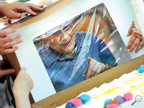 Vera Mastrantonio, a resident of Riverview Point Apartments in Catawissa, looks through the cellophane top of a box that covered her birthday cake Thursday afternoon during a party to celebrate her 100th birthday. Mastrantonio will be 100 years old on Monday, June 26.