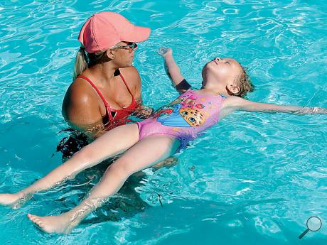 Knoebels lifeguard Kelsie Stewart, Shamokin, assists Maylen Zarko, 6, Elysburg stay afloat on her back during the park's annual Learn to Swim program Tuesday morning. Swimmers have a chance to take advantage of a ten-day program that familiarizes the children with all aspects of swimming.