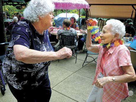 "Edie Shoffler, left, 83, and Vera Mastrantonio, 97, dance to the Beach Boys song ""Little Deuce Coupe"" played by Billy Dee and Rosie during a Hawaiian Luau on the patio at the Riverview Point senior high-rise apartments in Catawissa on Thursday."