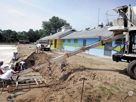 A crew with general contractor and designer Boyer Swimming Pools, of Millersburg, works in the concrete being poured from a Dan-Ber Concrete truck at the Ber-Vaughn Pool during reconstruction on Thursday.