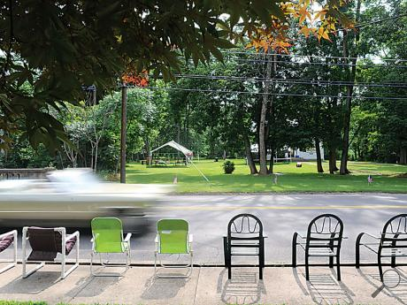 A car passes by chairs which are set up Friday afternoon in front of 433 North State Street in preparation for Saturday morning's Fourth of July parade.