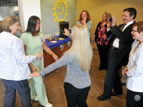 Geisinger pediatric nurse Cassie Thomas, second from left, reaches out to hug Kimberly Duffy, third from left, after hugging Kay Bower during a surprise reception for Thomas on her first day back to work at the Janet Weis Children's Hospital from vacation. While on vacation, Thomas help save the live of a boy on a beach who had been struck by lightning.