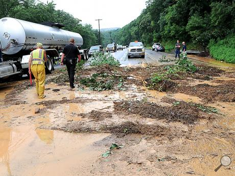 Fire police and Mahoning Township police walk across about 8 inches of mud that slid down the side of the bank along Route 11, near Bald Top Road, Monday afternoon. It made Route 11nearly impassable.