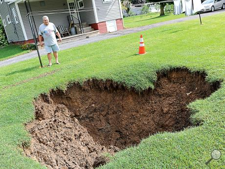 Joe Diehl ofLindbergh Avenue, Mahoning Township, stands Tuesday morning near a sink hole in his backyard which expanded during Monday's heavy rains.