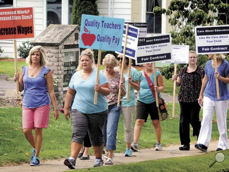 Millville teachers carry signs while walking a picket line along Main Street on Wednesday morning.