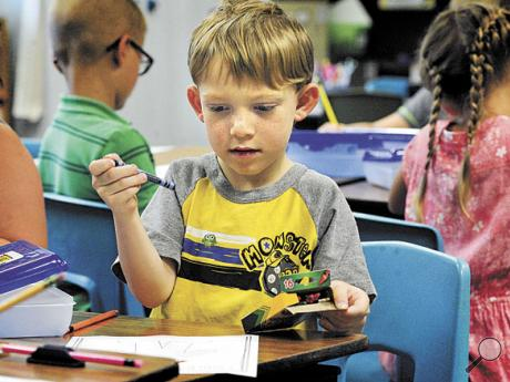 """Beaver-Main Elementary School first grader Hunter Fritz selects a Crayon to color his """"I can be a good listener"""" paper in teacher Megan Shields' class during the first day of school for the Bloomsburg Area School District on Monday."""