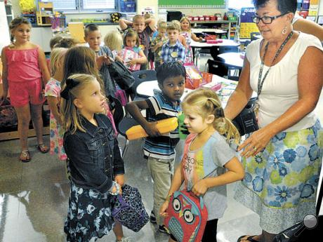 Danville Primary School kindergarten teacher Mary Lou Potter organizes her students into a line to walk to the cafeteria for lunch on Wednesday during the first day of school for the Danville Area School District. Children in the front of the line are, from left, Tenley Loper, Sashreek Suresh and Ruby Bowie.