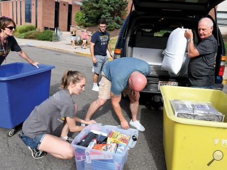 Rep. David Millard, right, and new Bloomsburg University provostDiana Rogers-Adkinson, left, assist the Goudeaux family as they help their son move into Elwell Hall Tuesday morning at Bloomsburg University. Also assisting is Tessann Merkel and Goudeaux's father, Matthew. Classes at Bloomsburg University begin onMonday.