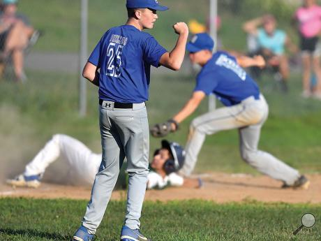 Berwick's pitcher Cole Phillips, foreground, reacts after his teammate Alex Peters, right, got the tag on the Back Mountain's Mike Timinski after Timinski tried to advance to thirdin the fourth inning of Wednesday evening's Junior RBI game in Berwick.