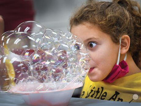 Avery Longnecker from Wee Little Angels Daycare, South Centre Township, is wide eyed as she blows up a tray of bubbles during the fourth 4-H program for the kids Wednesday morning at Sawmill Road. About 20 children attended the camps that taught them about sports nutrition, outdoor adventures and crafts.