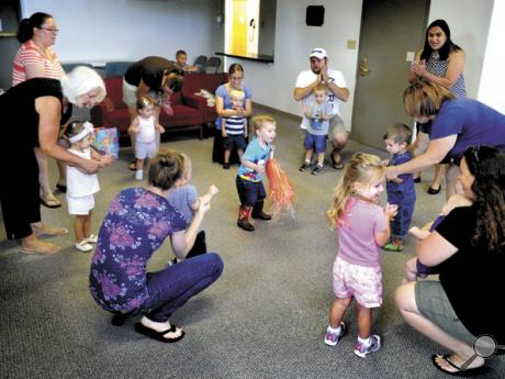 Parents and caregivers sing and move with their children during the Music and Movement for Toddlers weekly get-together at the Thomas Beaver Free Library in Danville on Tuesday morning.