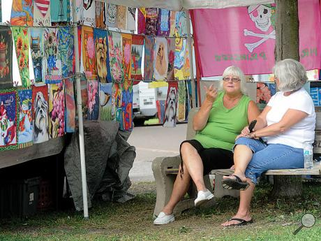 Donna Jones, left, and Becky Wojtowicz sit and talk on a bench at All Home Days while waiting for runners in Monday morning's 5K in Elysburg.