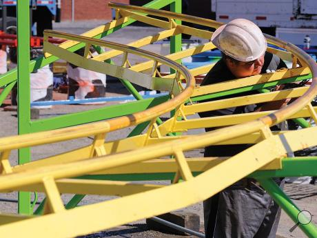 Reithoffer ride work Dan Friedman places pins in hooking sections of track together while building the Western Mouse roller coaster on the Bloomsburg Fairgrounds Wednesday afternoon.