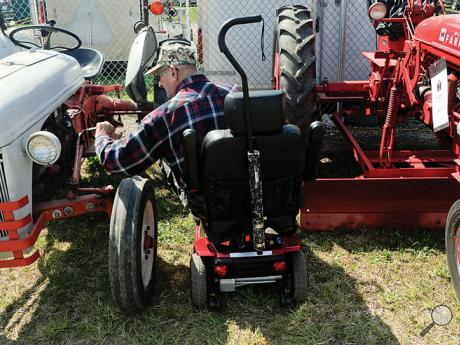 Claude Hagerman, Stroudsburg, looks at a 1952 Ford tractor along Machinery Row on the Bloomsburg Fairgrounds that is very similar to one he has back on his farm.