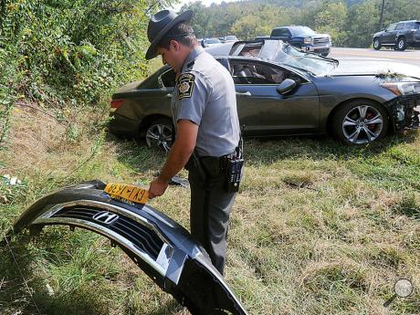 Trooper Steven Krasucki holds the bumper of a car that was ripped off in a crash while reading the license plate number over his  portable radio Tuesday afternoon along Route 42 in Henlock Township.