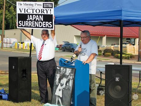 Dave Kovach, chairman of The Berwick Stuart Tank Committee, left, holds a headline from the September 2, 1945 issue of The Morning Press as treasurer Tom McLaughlin speaks during the official dedication of the Pennsylvania Historical and Museum Commission Historical marker honoring the Stuart Tank on Third and Oak Streets in Berwick on Wednesday evening.