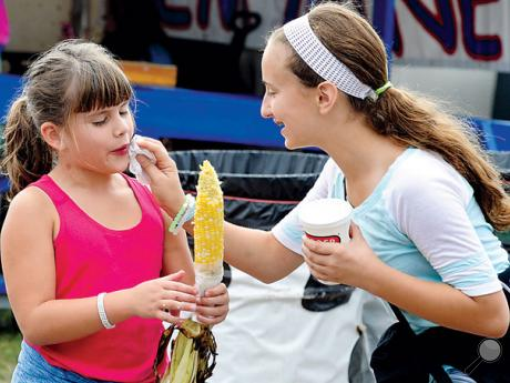 Makenna Thompson, right, 12, of Nescopeck, wipes some stray kernels of corn from the face of her cousin, LexiFedder, 7, of Berwick, as they tour the Bloomsburg Fair together on Wednesday.