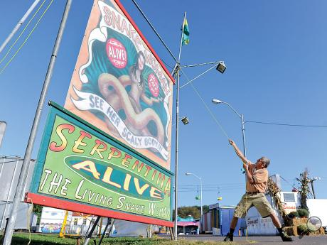 """Laszlo Kolozsy, raises the banner for """"Serpentina, The Living Snake Woman"""" at the Bloomsburg Fair Wednesday morning. Kolozsy, 64, said he was born in a circus wagon in Central Europe and has been working in the industry ever since. The Bloomsburg Fair opens tomorrow."""