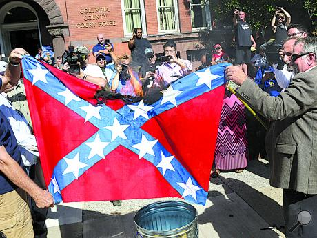 Supporters of Gene Stilp hold his homemade Nazi-Confederate flag as it burns Friday afternoon outside the Columbia County Courthouse.