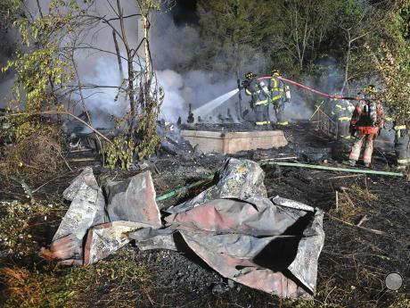 Berwick firefighters hose down the charred ruins of an abandoned home in Briar Creek Township early Friday morning.