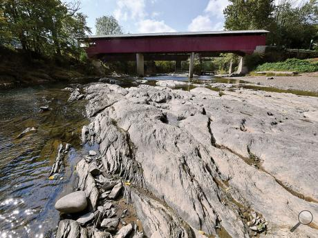 Rocks which are normally covered by water are exposed across most of Fishing Creek just down stream of the Rupert Covered Bridge Monday.
