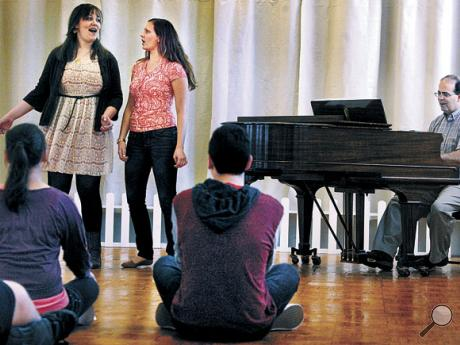 Southern Columbia High School junior Olivia Bodner, left, sings The Impossible Dream with Elise Mark, a private voice teacher from Danville, during a musical theater and singing techniques class that was part of The Bloomsburg Theatre Ensemble's annual High School Theatre Workshop day on Wednesday. Playing the piano is Bloomsburg High School choral director Tim Latsha.