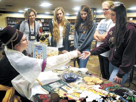 Society for Creative Anachronism member Jessica Charles, left, of Lewisburg, passes an aroma sample to Danville High School senior Kendra Foust during a visit with senior English students in the school library on Tuesday.